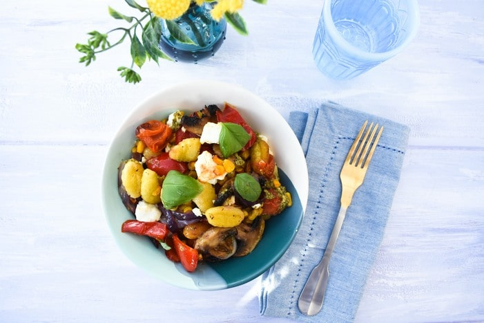 Roasted Vegetable Gnocchi Bake served in a pale blue with a blue napkin and fork