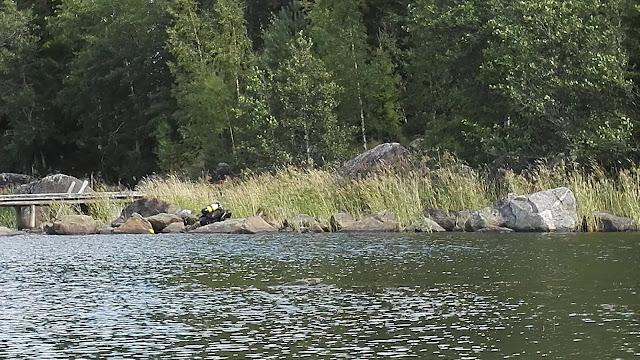 Sukeltaja makaa rantakivikossa.