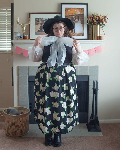 An outfit consisting of a wide brim black hat, a white organza blouse with a large bow tie under a black sleeveless dress that is tucked under a white and green floral on black maxi skirt and black chelsea boots.