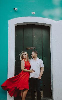 Pareja de novios delante de una puerta, ella con un vestido rojo y el cabello suelto