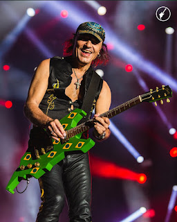 Matthias Jabs no palco tocando a icônica guitarra verde com bandeirinhas do Brasil, utilizada na edição de 1985.