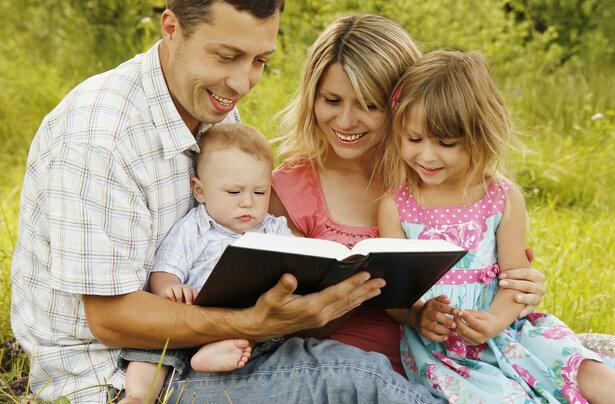 Padres cristianos enseñando la biblia a sus hijos