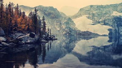 Lago bonito con bosque y montañas de fondo