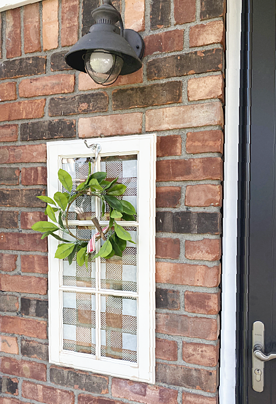 stenciled window with a wreath outdoor on brick