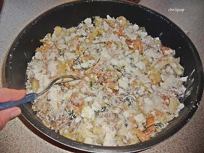 Ταψί που έχει μέσα ρύζι κιμά και τυρί τριμένο ,ενω ενα κουτάλι ετοιμάζεται να ρίξει φρυγανιά τριμένη