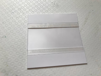 A piece of acetate stuck to the front of a white square card covering the middle cut out section