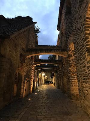 En trang, mørk gate med buer mellom steinbygningene.
