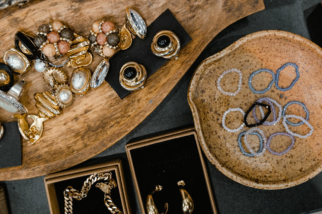 Various jewelry displayed on wooden dishes.