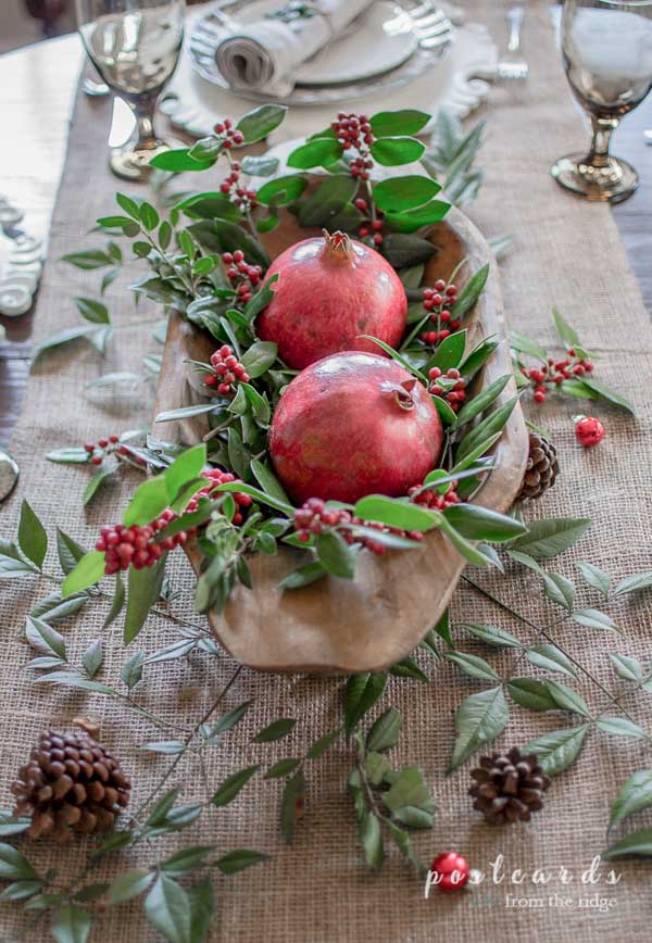 Christmas table centerpiece with pomegranites and holly in a wooden dough bowl