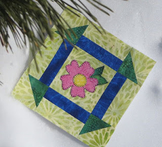 pink flower on a green quilt block