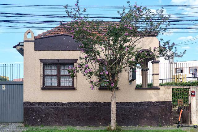 Casa de madeira e com fachada em alvenaria junto à calçada