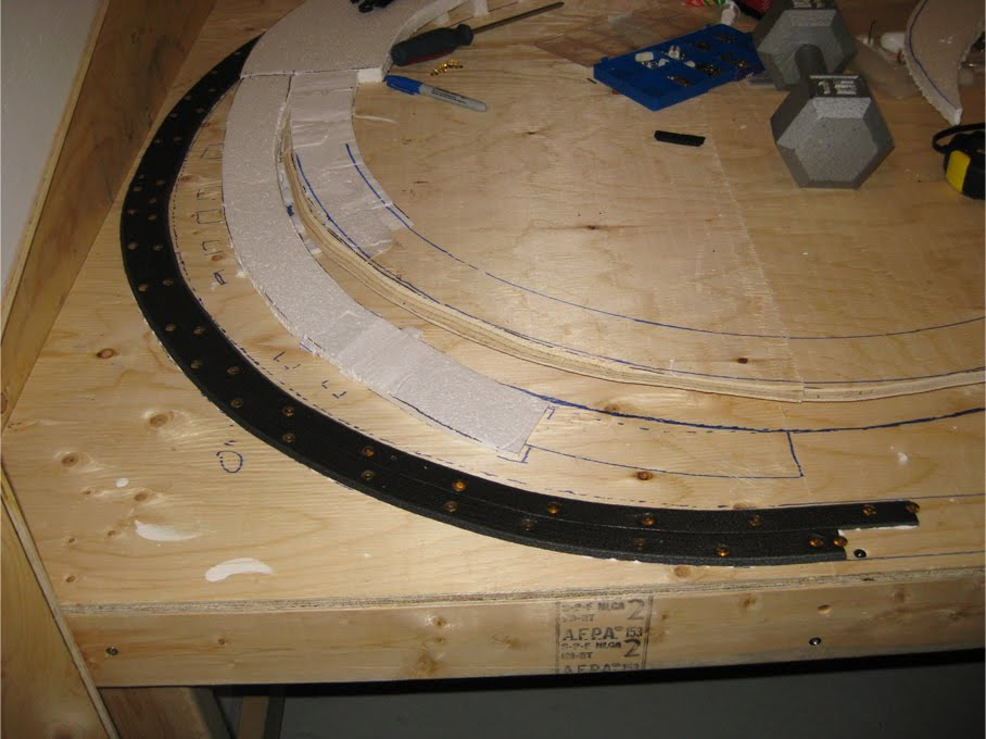 Foam trackbed installation using thumb tacks to hold it in place while it dries
