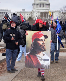 Protesters in front of U.S. Capitol, including woman in MAGA hat carrying poster with Jesus in a MAGA hat
