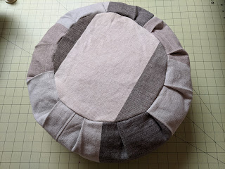 Top view of stuffed dark gray and off-white round meditation cushion