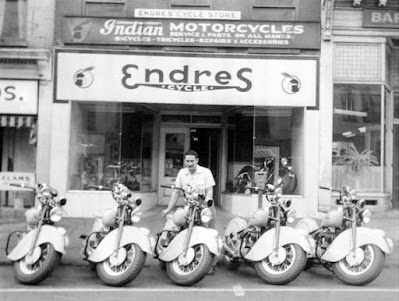 Man poses with motorcycles outside storefront.