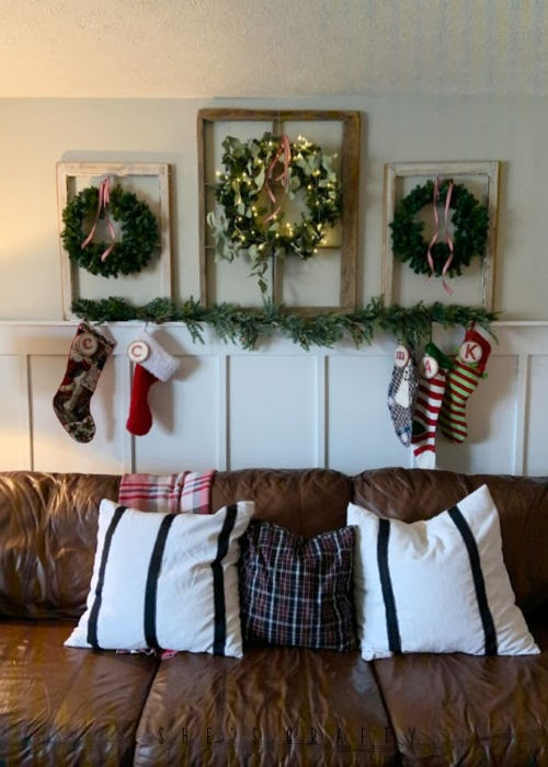 Vintage Christmas Decor Vignettes  |  see various ways to use vintage Christmas pieces in your home decor   |  living room,brown leather couches, board and batton, vintage windows with wreaths on long wall