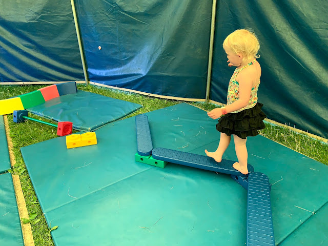 A toddler walking a long a plastic wiggly balancing beam in a gymnastics tent at 3 foot people festival