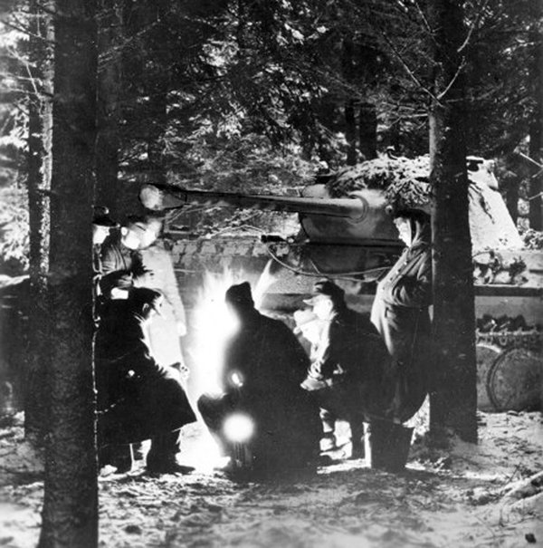 German soldiers around a campfire beside a Panther tank, somewhere in the Ardennes, Belgium,1944-1945 .