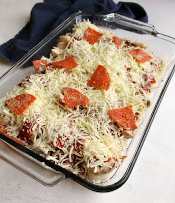 pan of bubble up pizza covered with shredded mozzarella and pepperoni ready to be baked