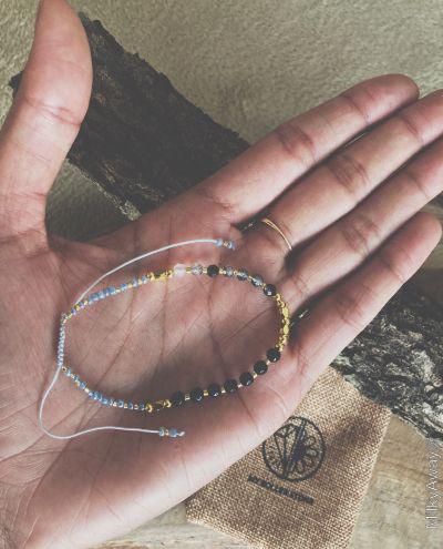 Bracelet fin en pierres naturelles d'onyx et de quartz rutile tourmaline My Roller Stone et son pochon en jute