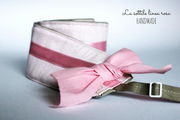 Fotografia di una tracolla rosa con fiocco per macchina fotografica realizzata artigianalmente