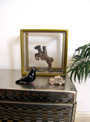 Art deco style modern miniature silver sideboard with a display case containing a horse and rider statue, and a glass bird and silver car ornament displayed in front of it.