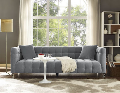 Grey velvet sofa with white throw pillows