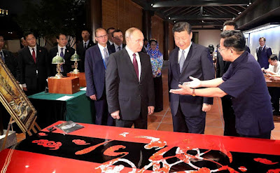 Vladimir Putin with Xi Jinping watching an exhibition of Chinese arts and crafts.