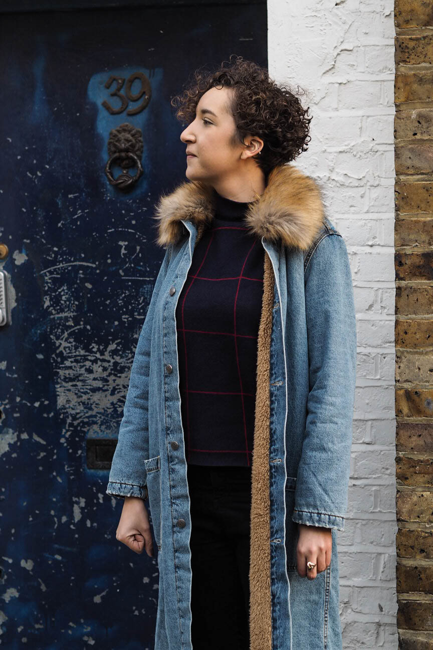 Fashion blogger wears long denim coat with faux fur collar
