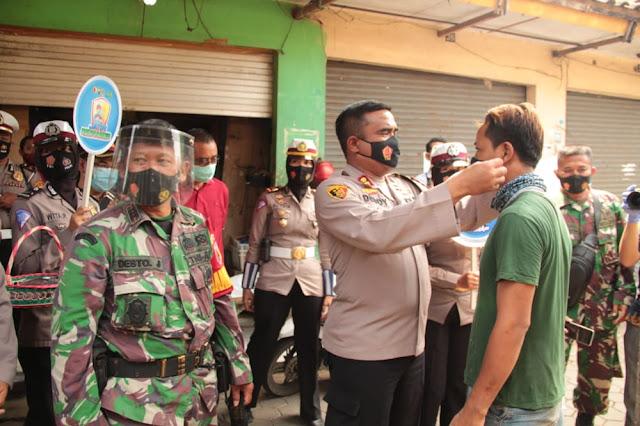 """Mojokerto - majalahglobal.com : Upaya pencegahan dan peningkatan kewaspadaan untuk mengantisipasi penyebaran virus Covid-19, dilakukan oleh Polresta Mojokerto dengan menggandeng IMM Toyota Mojokerto.  Sebagaimana yang dilaksanakan pada Jum'at (7/08/2020) Kapolresta Mojokerto mengkampanyekan Jatim Bermasker di Pasar Burung Jalan Empunala, Kecamatan Magersari, Kota Mojokerto.  Kampanye Jatim Bermasker ini dilakukan Polresta Mojokerto dengan menggandeng IMM Toyota Mojokerto dalam bentuk kegiatan Membagikan Masker dan Hand Sanitizer.  Masker yang dibagikan sebanyak 500 masker dari Polresta Mojokerto dan 100 botol Hand Sanitizer dari IMM Toyota Mojokerto.  Kapolresta Mojokerto AKBP Deddy Supriadi di dampingi Pimpinan IMM Toyota Bpk Munawar Tobing dan Kepala bagian Administrasi Bpk Sanyoto menjelaskan bahwa Masker saat ini menjadi kebutuhan masyarakat yang harus dipakai setiap hari dalam beraktifitas baik di rumah maupun keluar rumah.  Masker yang digunakan dengan benar dapat membantu Pencegahan Virus serta Bakteri yang menyebar melalui lendir atau yang keluar saat kita bersin dan batuk.  Dengan menggunakan masker kita sudah 60% mencegah penyebaran virusnya, ditambah menggunakan Hand Sanitizer 10%, Cuci tangan dengan sabun di air mengalir 10% dan Jaga jarak 10%, sehingga kalau kita melakukan semua protokol Kesehatan, insya allah 90% kita terhindar dari virus corona  Aparat keamanan baik TNI-Polri dan unsur terkait tidak henti-hentinya melakukan Penertiban dan Pendisiplinan kepada masyarakat yang tidak mematuhi Protokol Kesehatan, maka dari itu untuk menekan angka sebaran covid-19, kita harus Disiplin melaksanakan dan mematuhi Protokol Kesehatan.  """"Ayo bersama kita Cegah Penyebaran Covid 19 dengan menggunakan Masker, Maskermu untuk melindungiku, Maskerku untuk melindungimu,"""" tutup Kapolresta Mojokerto AKBP Deddy Supriadi. (Katmanto/Jayak)"""