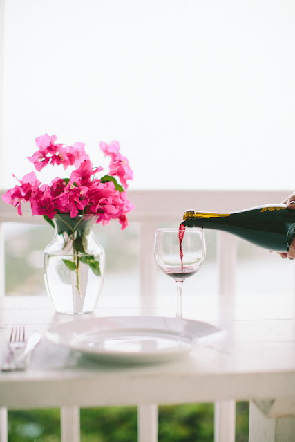 Setting a simple beautiful table with bougainvillea, wine and white porcelain dishes | Saint John, Virgin Islands