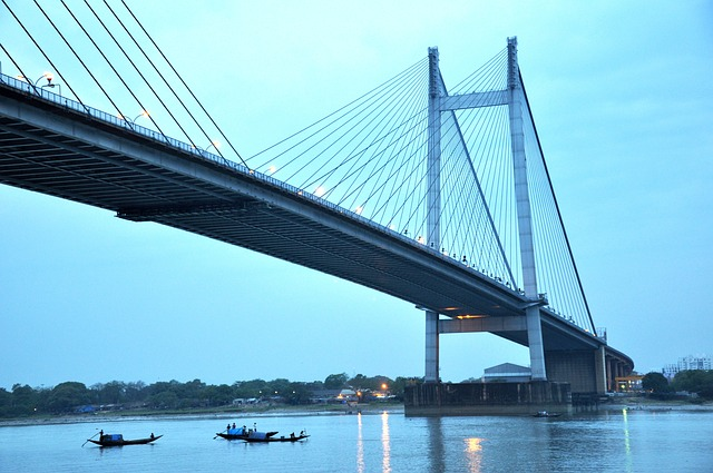 Kolkata Bridge on Hooghly River with several boats flowing under it