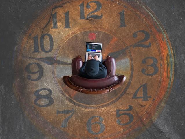 Vista superior de un hombre sentado en un sillón sobre un reloj pintado en el piso