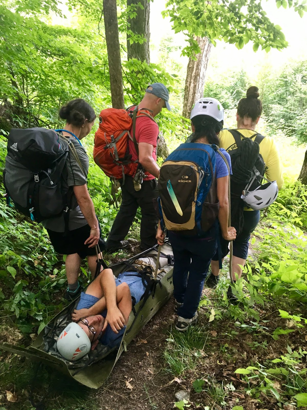 Four students in climbing gear carry another student down a hill on a stretcher. They are in a wooded area.