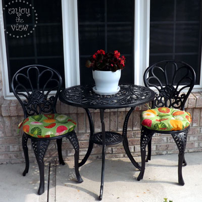 black wrought iron bistro set with brightly colored round seat cushions