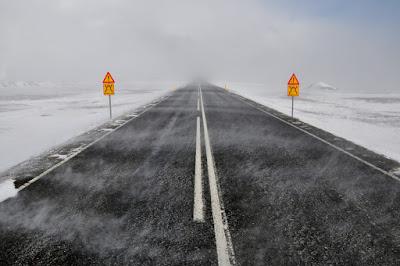 carretera con niebla y nieve al rededor y carteles de peligro al conducir en invierno por islandia
