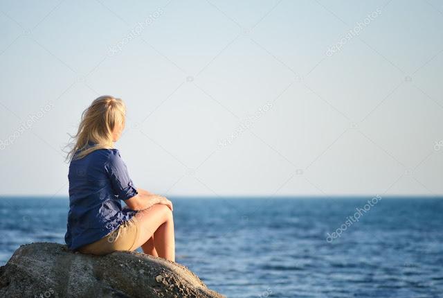 garota sentada sobre uma pedra olhando o Mar