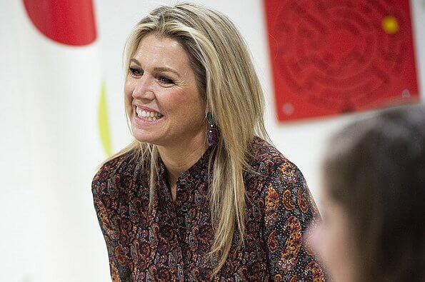 Queen Maxima wore an asymmetrical paisley print midi dress by Altuzarra, and red leather knee boots by Gianvito Rossi