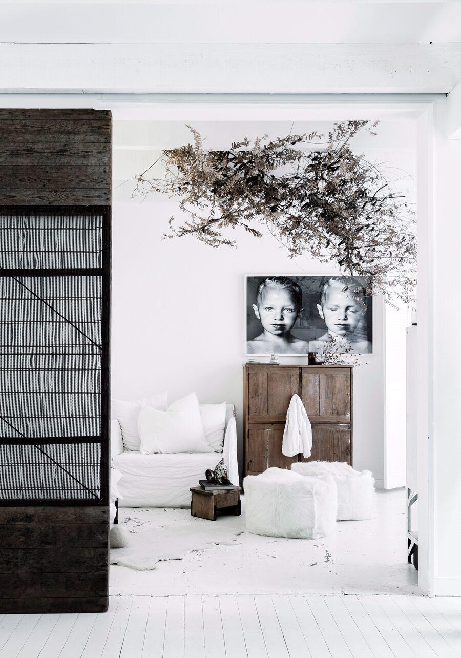 Salón blanco con muebles de madera oscuro y fotografías en blanco y negro