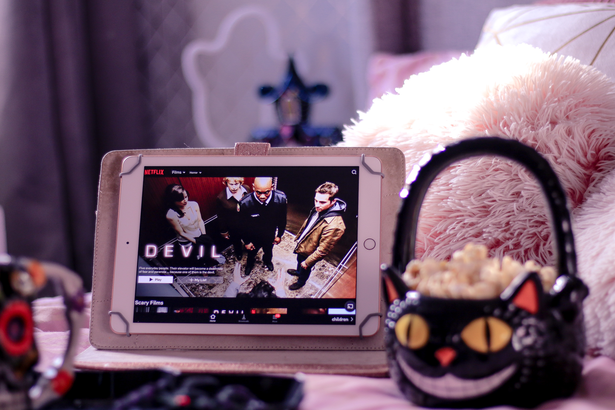 Close up photo of an iPad with Netflix uk on the screen with a black sugar skull to the left of the photo, out of focus.