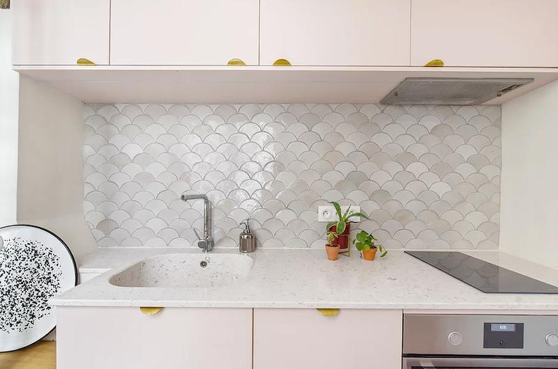 Cocina rosa con tiradores dorados, encimera de mármol y frente de azulejos con forma de escamas de pez.