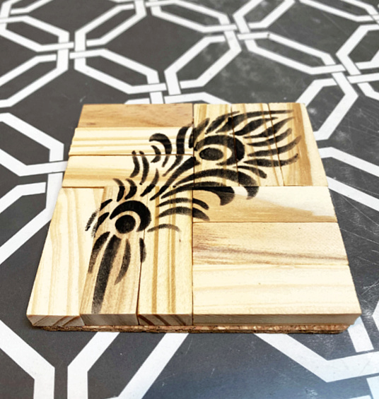 black feather stenciled on coaster
