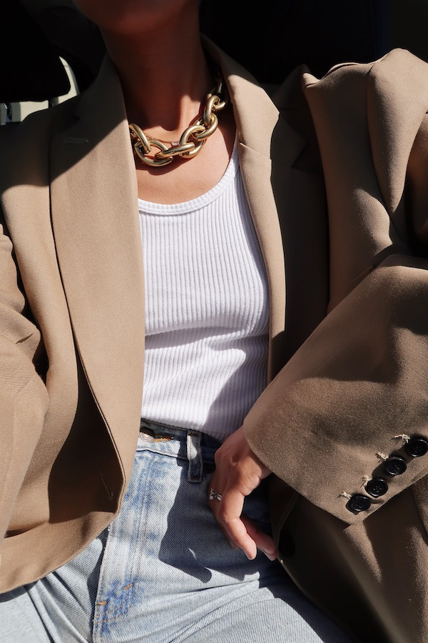 @shhtephs Instagram Spring Outfit Idea — chunky gold chain necklace, beige tan blazer, white ribbed tank top, high-waisted jeans