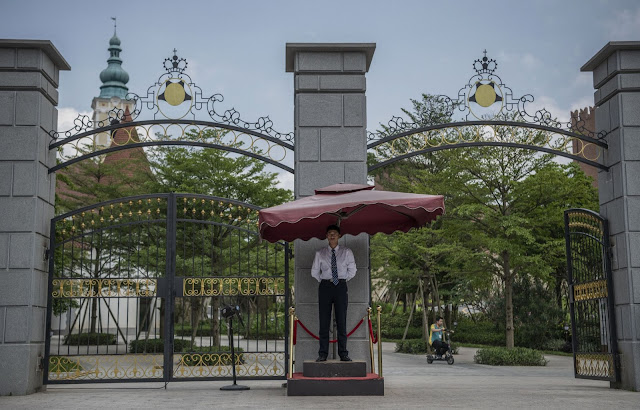 A Huawei security guard stands outside a gate