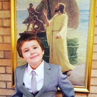 Dan Jon Jr in front of a picture of Christ and his Disciples