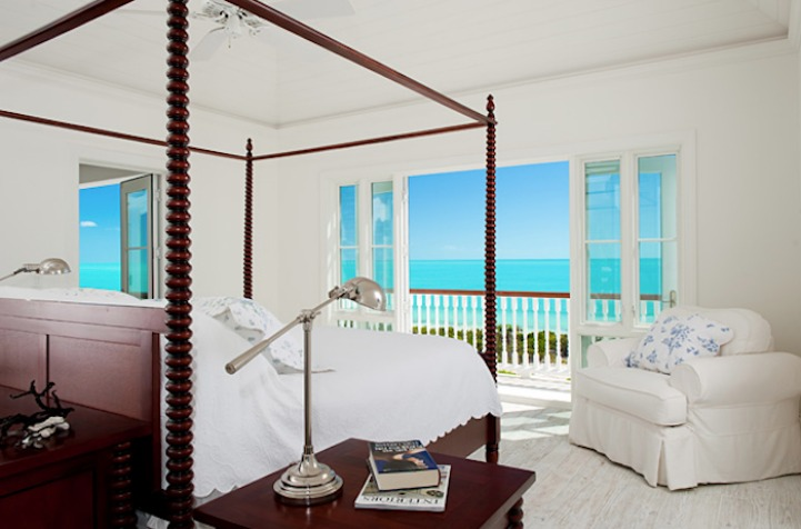 Coastal bedroom with four poster bed and an ocean view