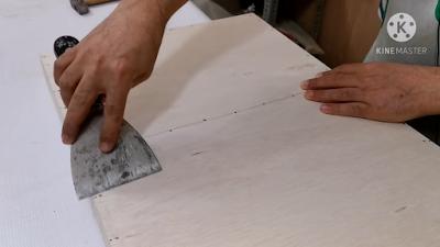 شخص يميك سكين معجون ويمرره على سطح الخشب لإكتشاف أي بروز بالسطح