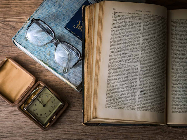 Bible with glasses and clock
