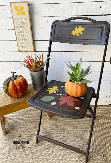 Photo of a rusty folding chair stenciled with fall leaves.