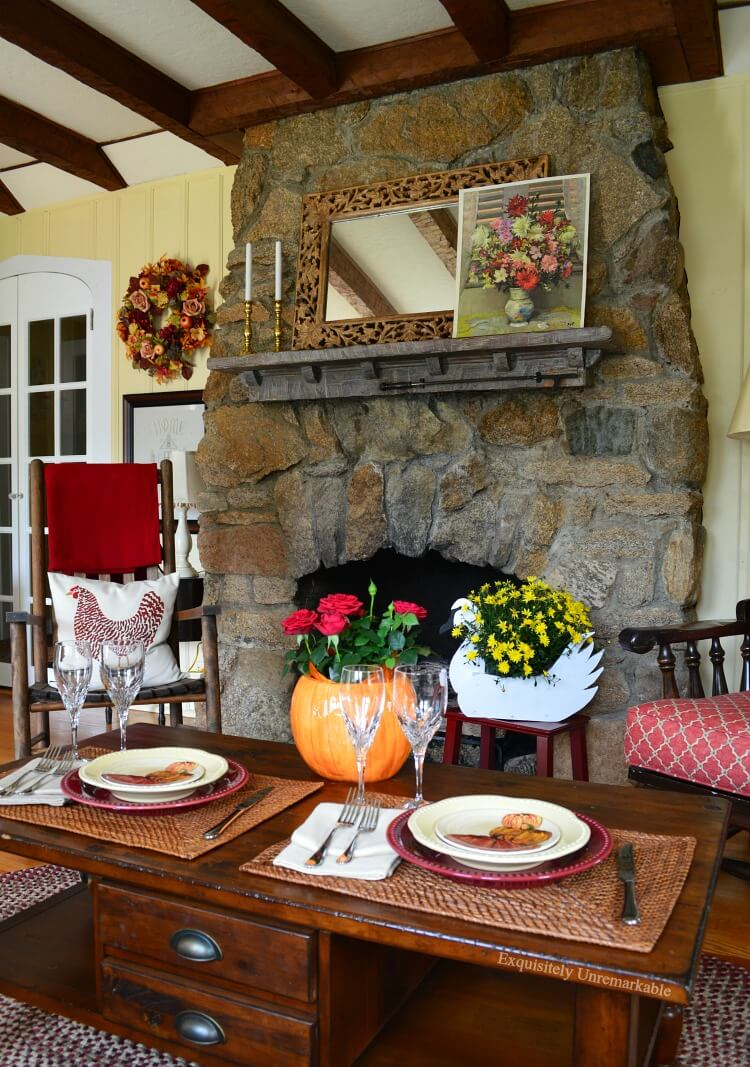 Living room with stone fireplace beams on ceiling and a fall table set with flowers and pumpkins